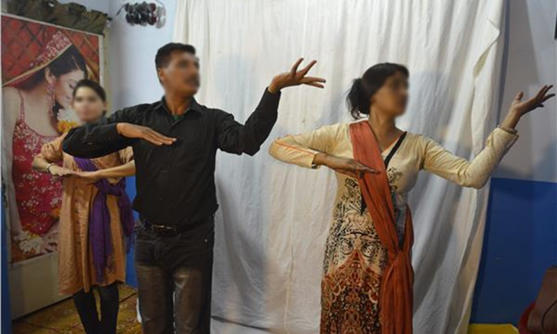Rashid Bhatti, a dance instructor, teaching students dance steps at his dance academy in Lahore ─ AFP