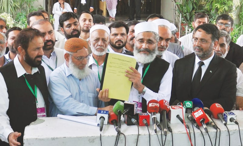 JI chief Sirajul Haq presents a copy of the party's petition to the media — Dawn/File