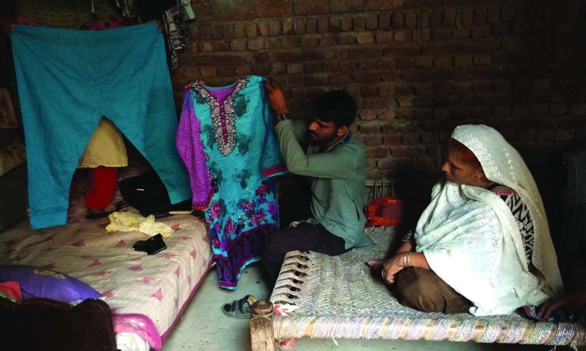 Taufiq Ahmed shows a dress belonging to his wife | Annie Ali Khan