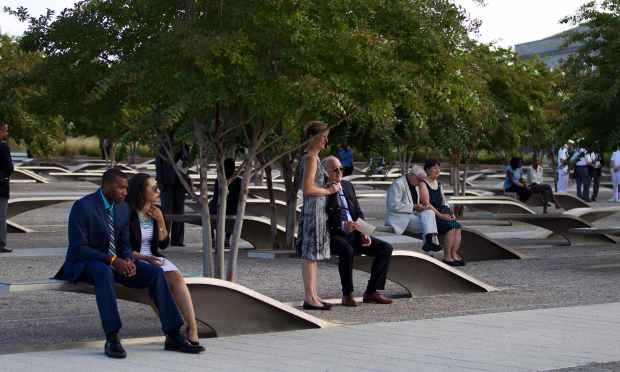 Family members sit on memorial benches before the observance ceremony to mark the15th anniversary of the 9/11 attacks at the Pentagon Memorial in Washington DC.  — AFP