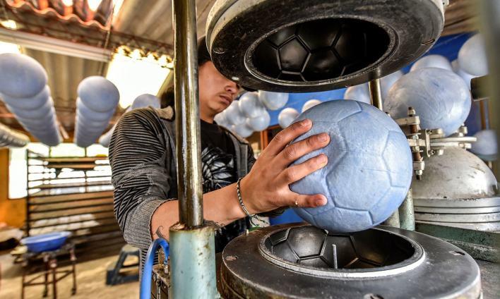 مینگوئی کی فیکٹریوں میں فٹ بال کے علاوہ مائیکرو-فٹ بال بھی بنائے جاتے ہیں—فوٹو: اے ایف پی