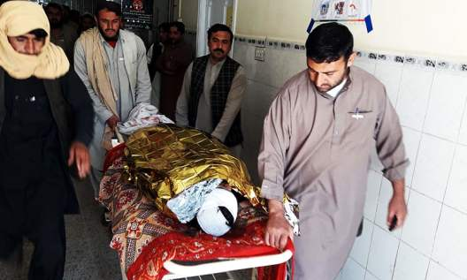 Pakistani relatives push a stretcher carrying the body of a victim at a hospital following cross border firing in the border town of Chaman. ─ AFP