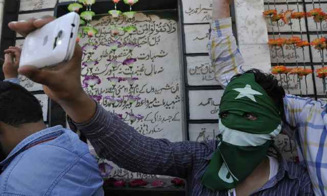 A masked protestor takes pictures during a protest rally in Srinagar on May 21, 2016