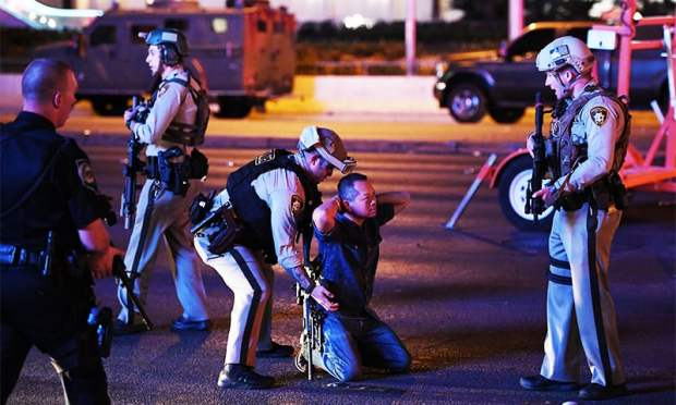 Police officers stop a man who drove down Tropicana Ave. near Las Vegas Boulevard and Tropicana Ave, which had been closed after the mass shooting at a country music festival. ─ AFP