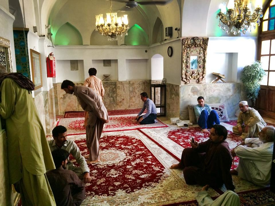 Pilgrims rest and pray in the room around Bibi Shahrbanu's tomb, located to the left of the picture.