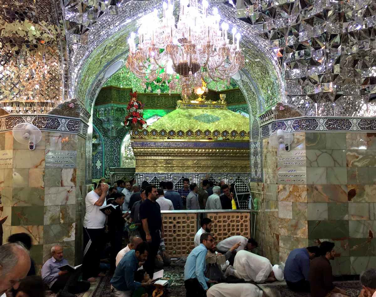 Worshippers pray inside the Fatima Masoumeh shrine in Qom. Her tomb can be seen in the background. Like all shrines in Iran, the space is divided exactly down the middle into men and women's sections.