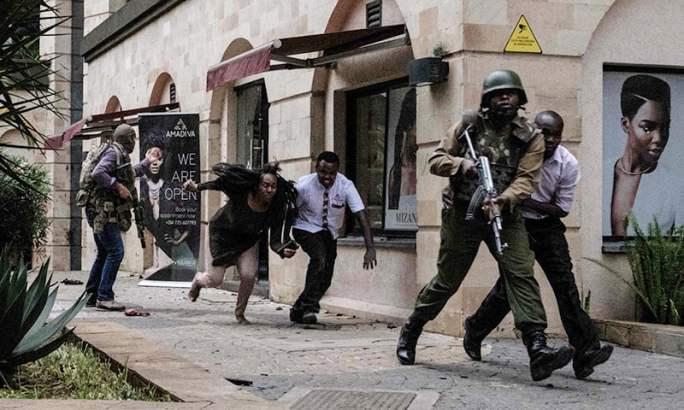 پولیس اہلکار ہوٹل میں پھنسی افراد کو باہر نکال رہے ہیں— فوٹو: اے ایف پی