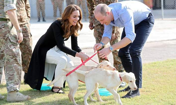 Prince William and Kate play with golden labrador puppies Salto and Sky as they visit an Army Canine Centre in Islamabad. — Reuters