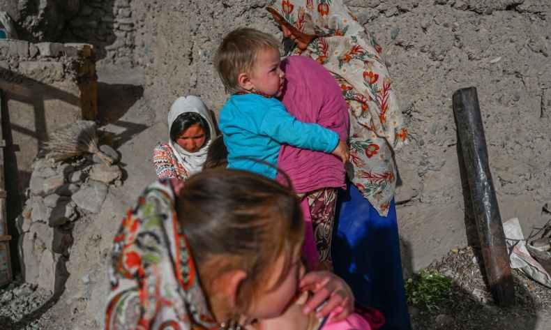 A Hazara woman stands with children on a cliff pockmarked by caves where people still live as they did centuries ago in Bamiyan, Afghanistan on October 3, 2021. — AFP