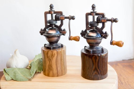 Foodie gift guide: wood salt and pepper grinders on a wood chopping board with vegetable on the side.