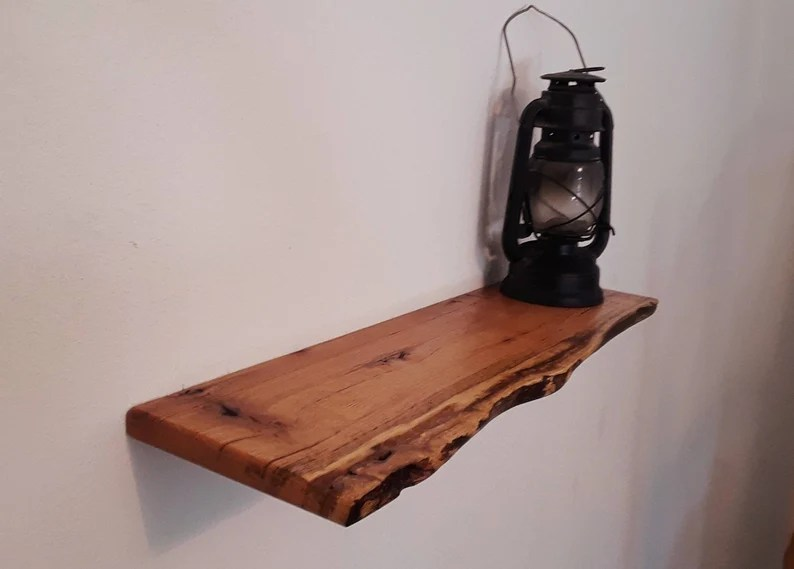 Photo of a wooden shelf affixed to a white wall with a black gaslamp sitting on top.