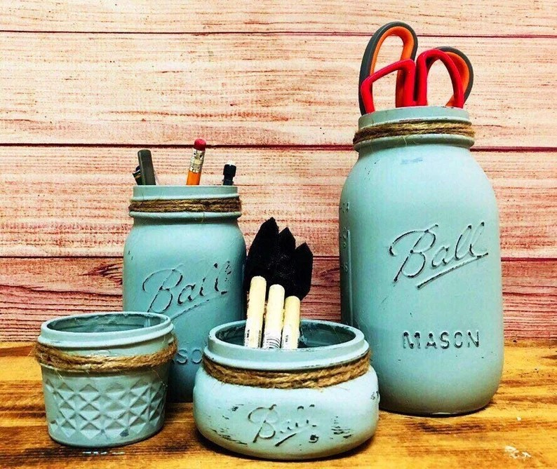 Photo of turquoise painted Ball brand glass jars with twine wrapped around the top. Jars have items in them, including scissors, pencils and pens. Jars are sitting in front of a wooden board background on top of a wooden-surfaced table.