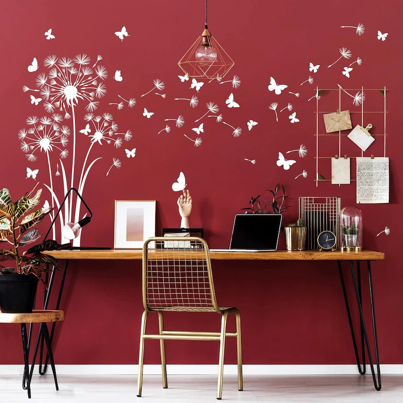 Photo of cozy home office desk set up with chair, burgundy background with images of butterflies on the wall.