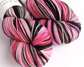 Hand dyed high twist superwash merino/nylon sock weight/fingering/4ply yarn. Tonks - variegated pinks, red, black and grey.