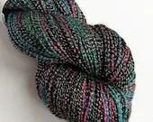 Hand dyed yarn, 100g of silver sparkle sock yarn, superwash merino/lurex 4ply/fingering. Bed Behaviour - black, pink, blue and yellow yarn.
