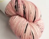 Indie dyed superwash merino/nylon/stellina sparkle sock yarn.  Hand dyed variegated peachy-pink yarn with black speckles.