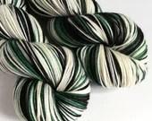 Hand dyed variegated 75/25% superwash merino/nylon sock fingering 4ply weight yarn, Draco - green, black, white and pale yellow yarn.