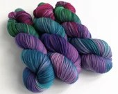 Hand dyed high twist superwash merino/nylon sock weight/fingering/4ply yarn. Moody Bird - variegated pink, blue, purple and green sock yarn.