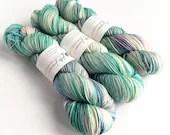 Hand dyed sport weight yarn 80/20% superwash merino wool/nylon,  Variegated icy blues, and pink.  Thick sock yarn.