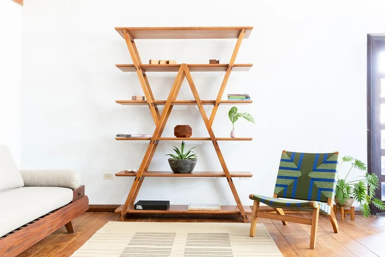 Photo of a wooden bookshelf that has geometric design with two plants and several small items sitting on it. Shelf is in a room with white walls and living room furniture, rug and houseplant.