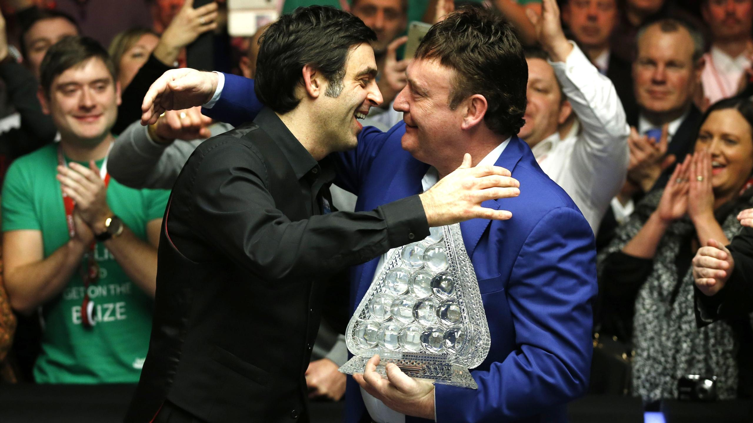 Jimmy White presents Ronnie O'Sullivan with the Masters trophy after victory in the final. Ronnie and Jimmy are Eurosport pundits at this week's German Masters.