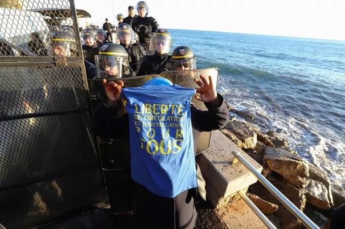 Un manifestant brandit un t-shirt sur lequel est inscrit