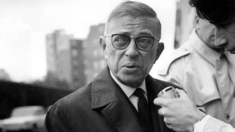 Jean Paul Sartre sortant du domicile de Simone de Beauvoir, est interviewé par un reporter après avoir refusé de recevoir le prix Nobel de Littérature, le 23 Octobre 1964.