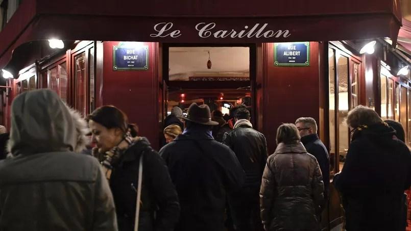Plusieurs personnes rassemblées devant le bar Le Carillon, un an après les attentats du 13 novembre 2015.
