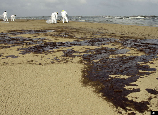 Workers clean up oil from the Deepwater Horizon oil spill on the beach at Grand Isle, La. Saturday, June 5, 2010. (AP Photo/Charlie Riedel)