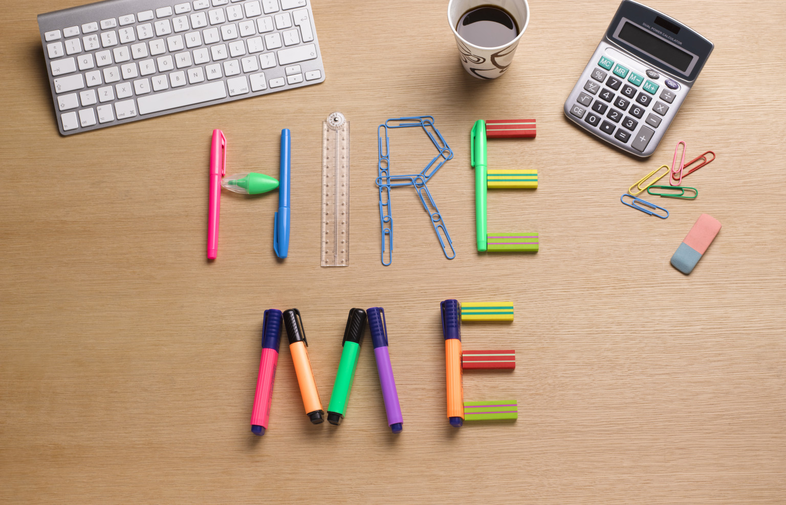 creative 'hire me' written using office stationery like pens, pencils, marker, eraser, calculator, coffee, paper clips