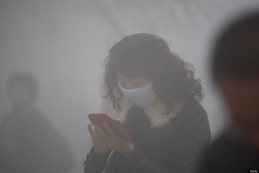 woman wearing a mask uses her mobile phone