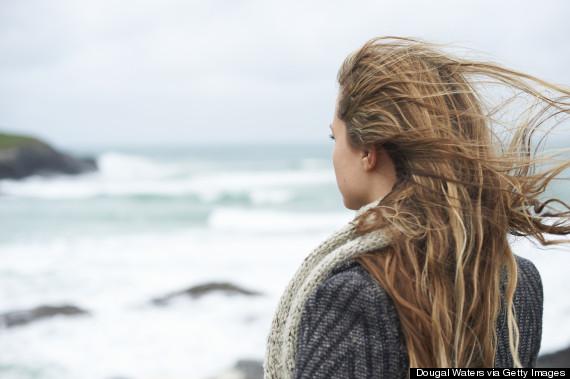 woman alone looking at ocean rear