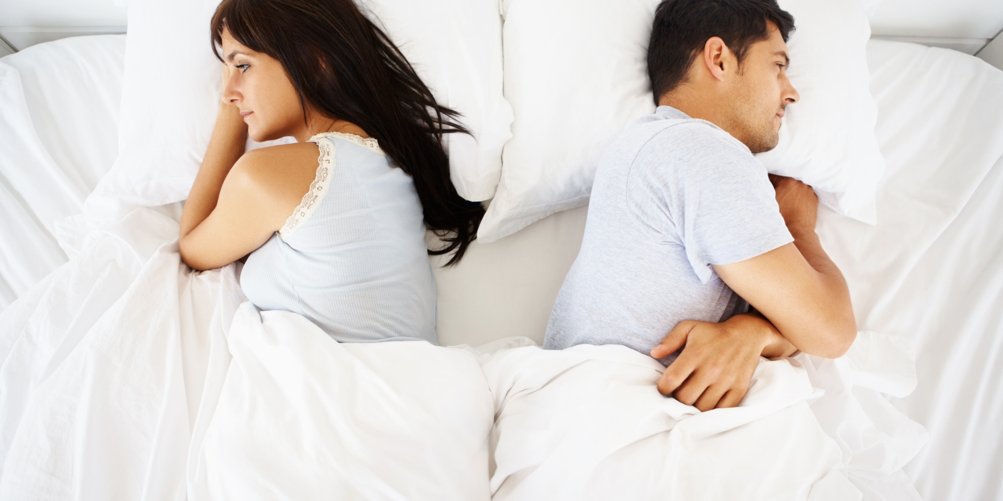 Couple in bed but apart