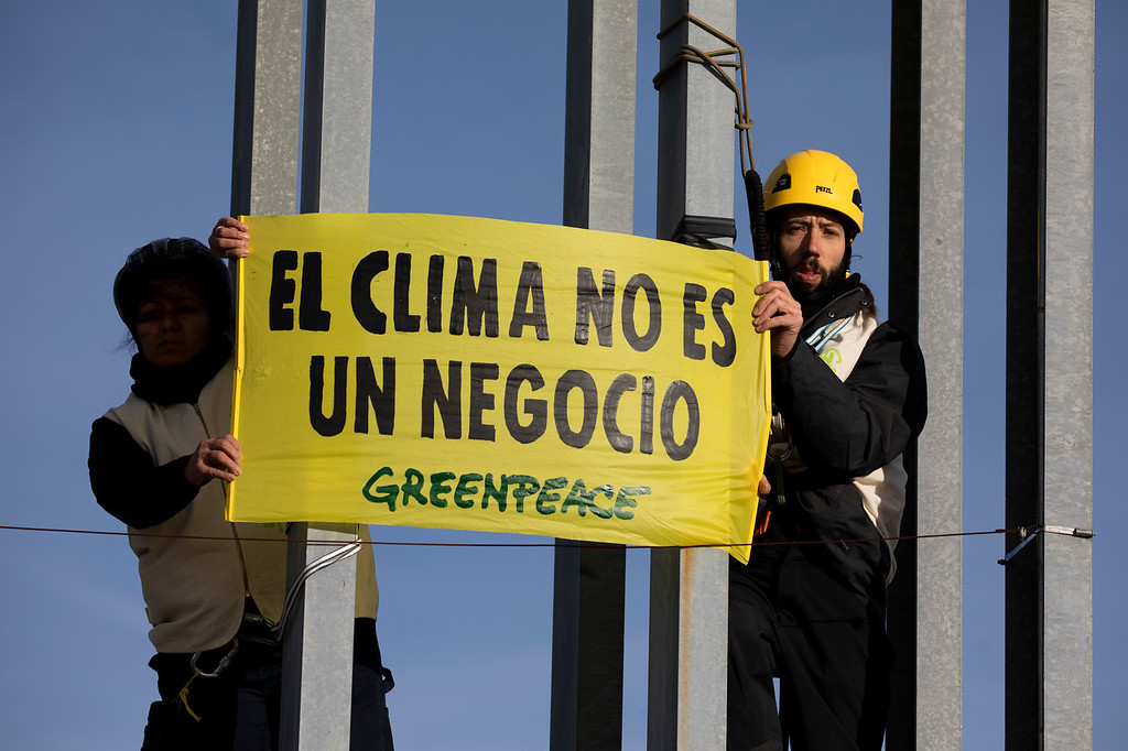 Escaladores de Greenpeace cuelgan varias pancartas frente a la COP para pedir un acuerdo justo y que no se negocie con el clima