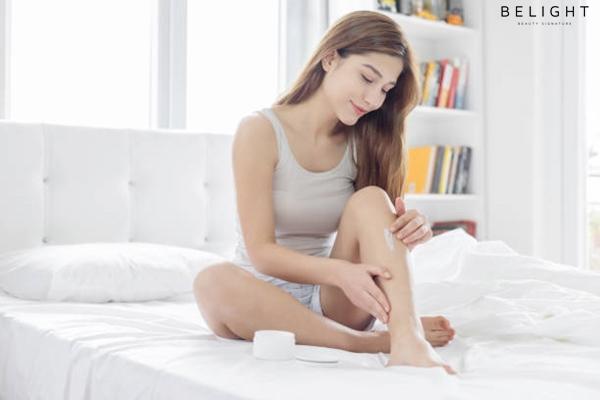 Young-woman-applying-cream-on-legs