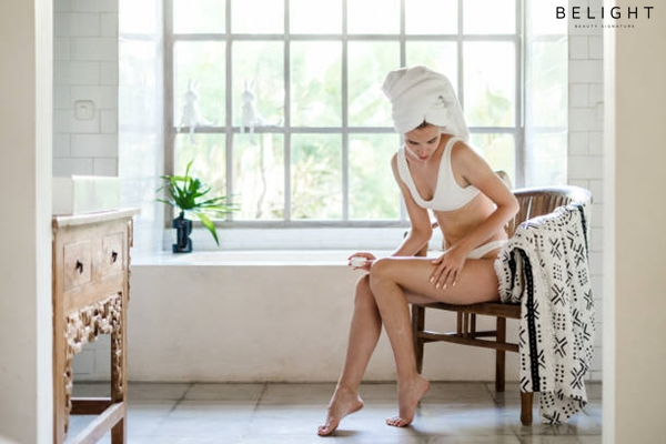 Young-adult-girl-with-towel-on-head-sitting-on-chair-in-white-bathroom-applying-soft-natural-cream-o