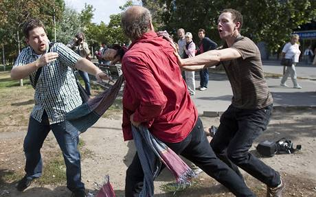 Blažek (center, in red), tries to fend off two journalists after felling his rival, Hejtmánek, lying in the background after being felled with a punch