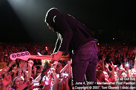 Pete Wentz from fall out boy on stage accepting flowers from fans.