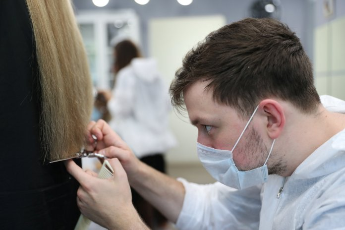 Hairdresser wearing face mask serves client in reopened hair salon on first day after lockout to curb the spread of coronavirus disease (COVID-19) was lifted in Moscow, Russia, June 9 2020. REUTERS / Evgenia Novozhenina