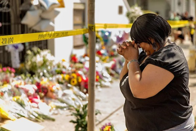 A woman weeps outside historic Mother Emanuel African Methodist Episcopal Church, June 19, 2015, in Charleston, S.C., after Dylann Roof, murdered nine people there during a prayer meeting. Now, survivors and families of the victims are asking a court to allow them to sue the federal government over what they say was a failed background check of Roof, allowing him to get the gun used in the shooting.