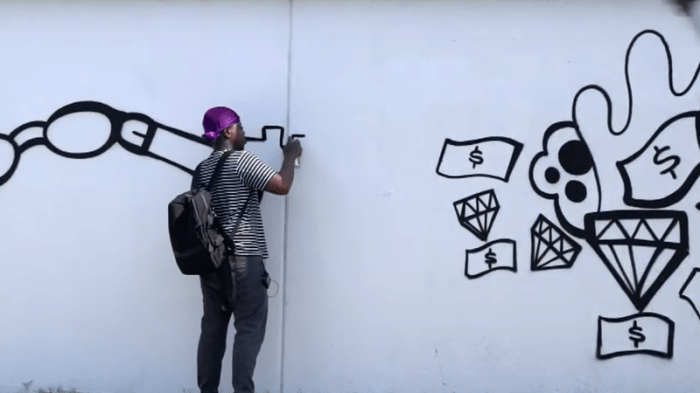 Sheefy McFly working on a mural in Detroit