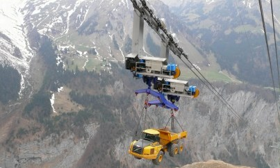 Truck transported on a ropeway going up a 5.400 - foot mountain