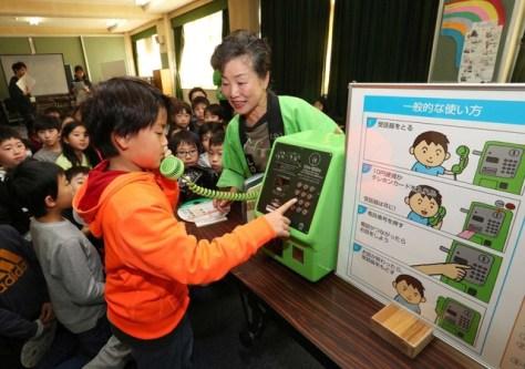 岡本美治さん(右)から公衆電話の使い方を教わる子どもたち=神戸市須磨区(撮影・大森 武)