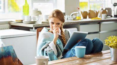 Eine verschnupfte Frau sitzt am Küchentisch mit einer Tasse Tee.