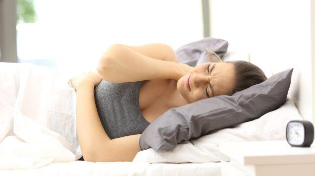 Eine junge Frau mit Schmerzen in Nacken und Rücken auf der Couch.