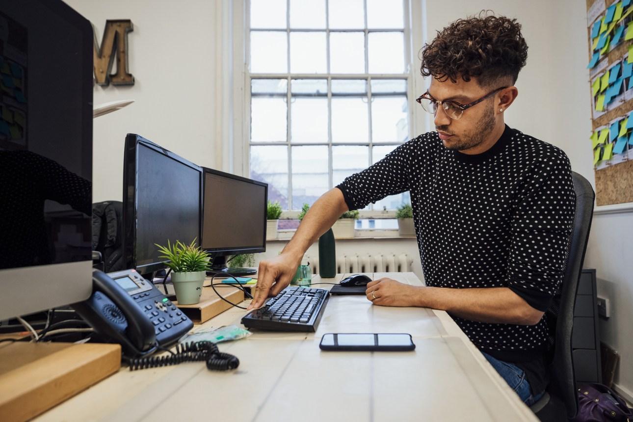 человек чистит клавиатуру настольного компьютера