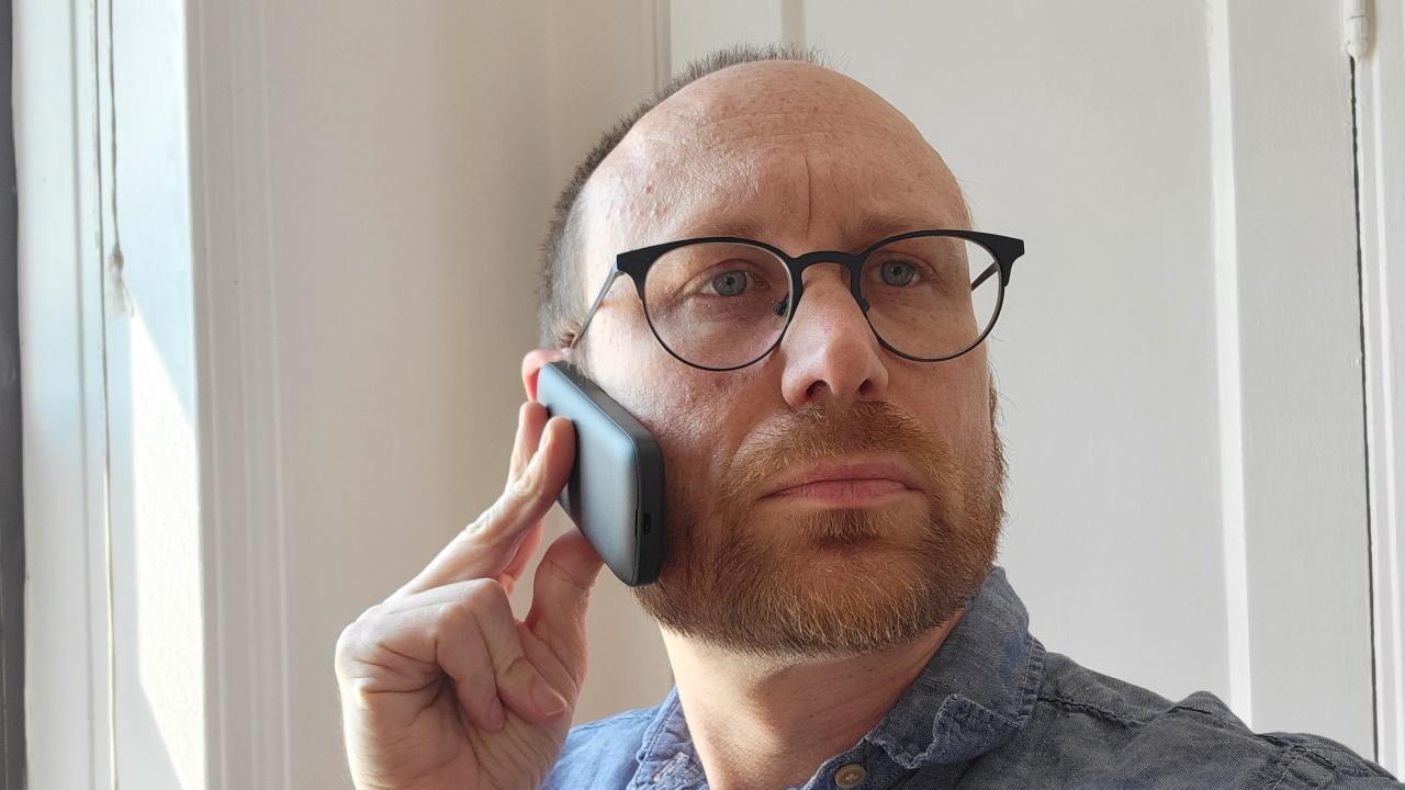 Человек, держащий телефон к лицу