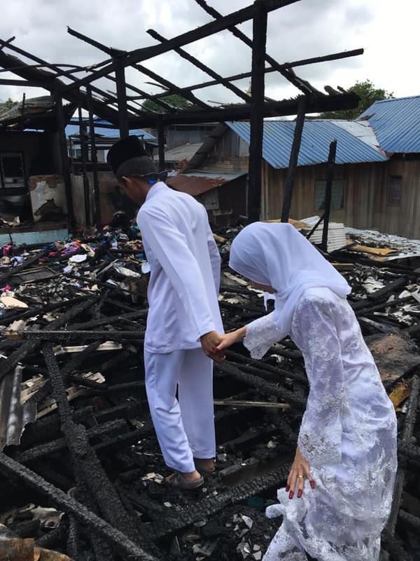Sepasang pengantin melawat rumah mereka yang terbakar