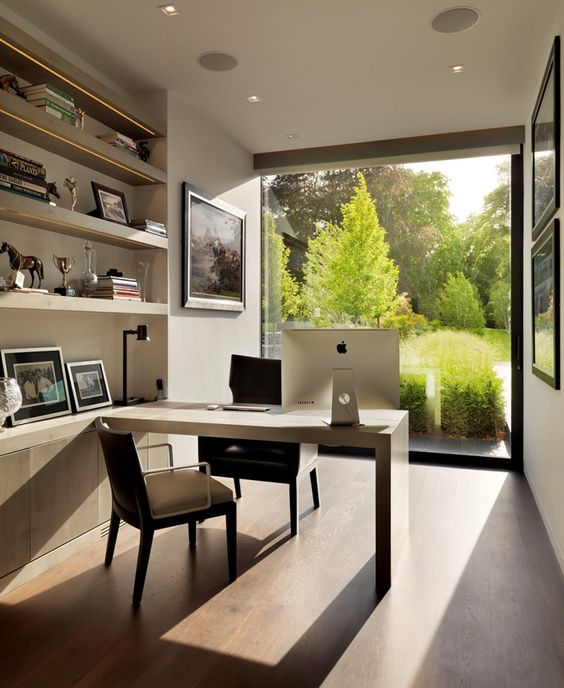a modern rather small home office with a glass wall coming to an English garden