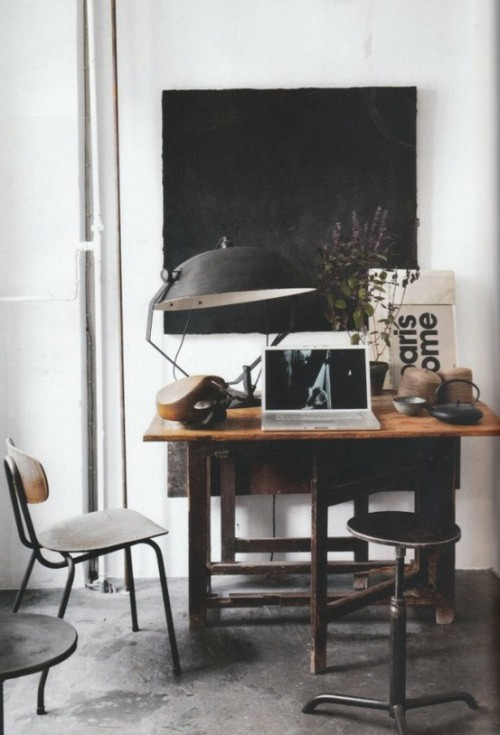 A vintage lamp, an old wooden desk and a stool from the last century make this small home office truly industrial.
